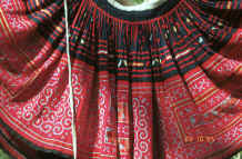 to Jpeg 54K Detail of Green Hmong (Lai Chau province, northern Vietnam) woman's skirt showing the waist gathering, applied strips of red fabric and small triangles to the top border and cross-stitch with applied floral rectangles in the bottom border 9510f27.jpg